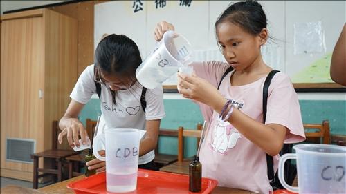 鳥松國中的同學神情專注地將界面活性劑倒入洗手乳罐裡