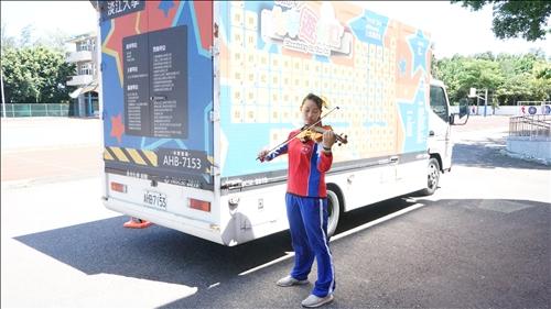 富禮國中的學生於化學車前完成她的小提琴表演