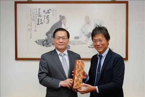 2-安達千波矢教授(右)贈送葛煥昭校長(左)禮品。(馮文星攝影)