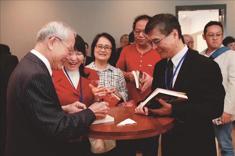 69週年校慶校友活動中,眾人恭賀陳定川獲名譽博士,並排隊邀請親簽《往高處行》一書。(攝影/高振元)