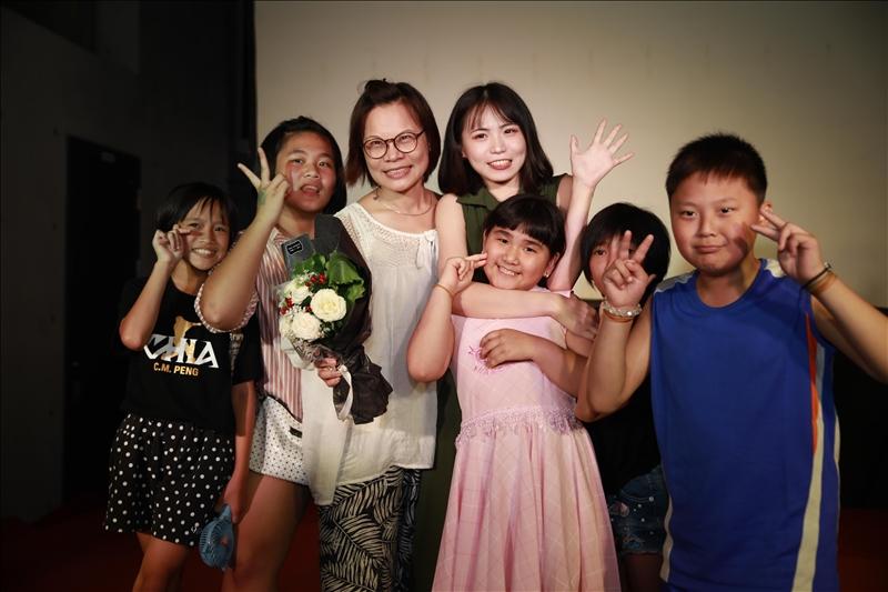 《放學後,回家前》紀錄片的主角李麗卿老師與小阿德課輔班學生,開心地與大傳系學生合影。