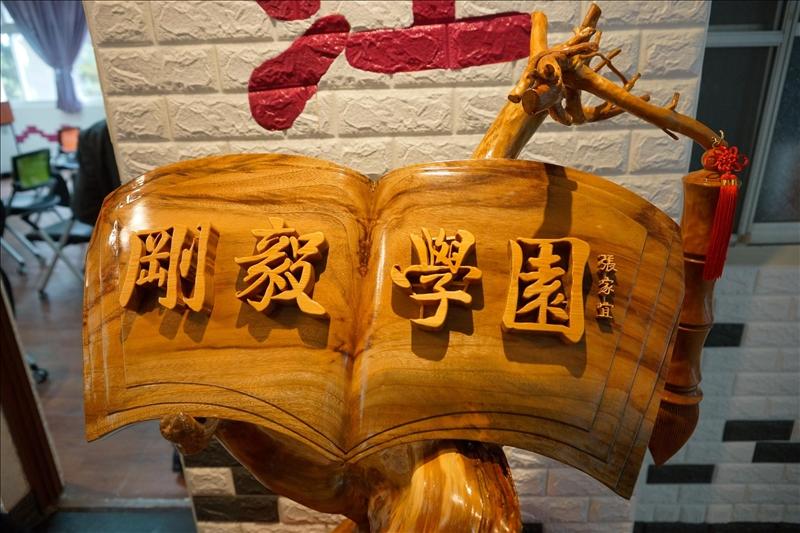 「剛毅學園」木雕品,由張前校長家宜題款(馮文星拍攝)