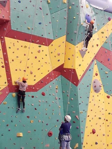 攀岩教練在岩場下指導並鼓勵師生向上攀爬的技巧