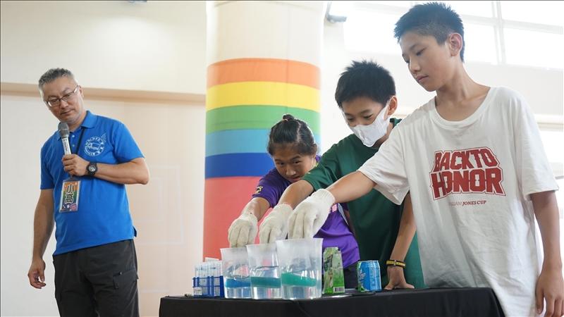 科教中心執行長高憲章指導學生上台示範「化學魔術秀」。(圖/科學教育中心提供)