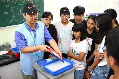 中華紙漿的工作人員在活動中教導同學彈紙之箋實驗的步驟。