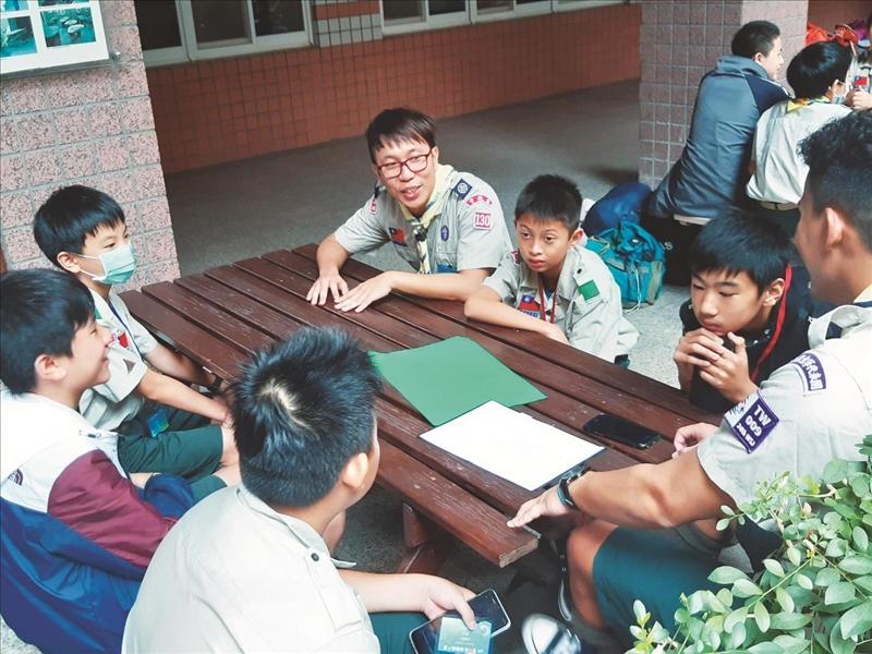 銅質翠竹獎章得主丁中甲校友(右四)與小隊學員討論分工。(圖/童軍團提供)