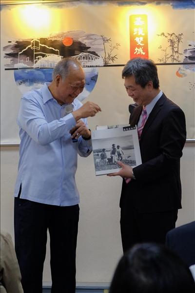 新北市政府顧問蔡葉偉捐出2本書給淡水維基館,由資圖系教授林信成接受。(攝影/連慧榕)