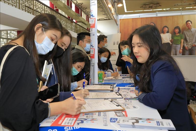 多位學生在徵才廠商攤位現場填寫求職履歷。(攝影/游晞彤)