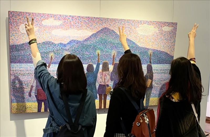 〈伴著紫紅色光影說YA〉主角群觀展時,再次開心地在畫作前比YA。(攝影/淡江時報社潘劭愷)