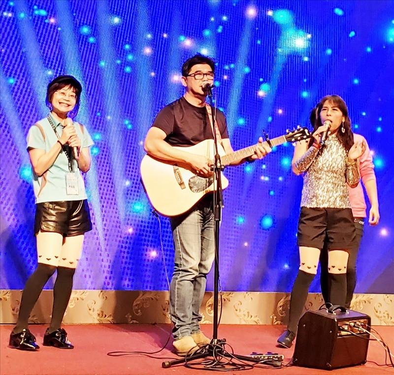 多才多藝的民歌王子,北加州校友會前任會長廖逸民(中)彈著吉他,帶領校友們回味學生時代。(圖/台北市校友會提供)