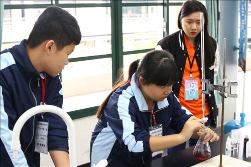 虎尾國中擔任助手的學生在淡江工作人員的協助下專注的操作儀器