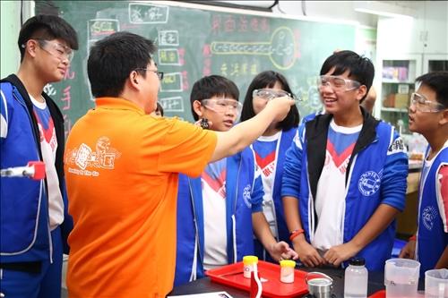 淡江工作人員正與旗津國中但任助手的同學們分享化學藥品的小知識