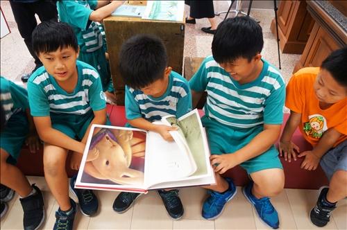 小朋友開心翻閱繪本故事書