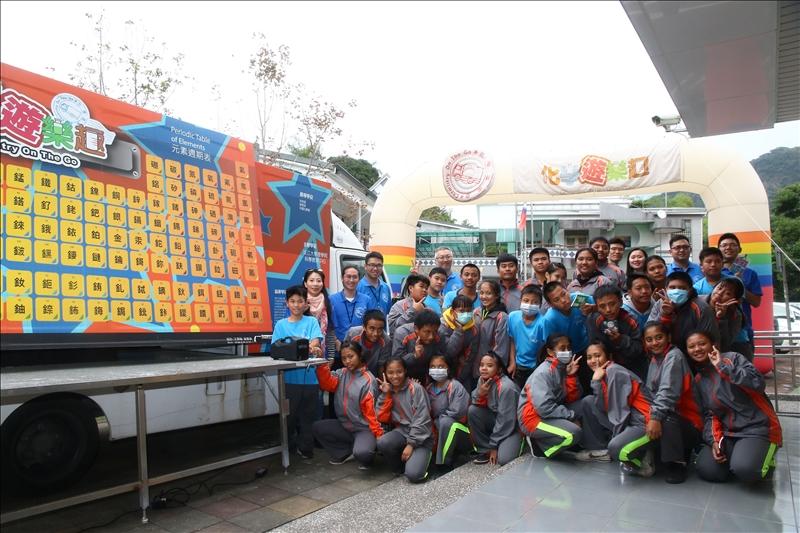 茂林國中的師生與淡江工作人員一起在化學車及拱門下合照