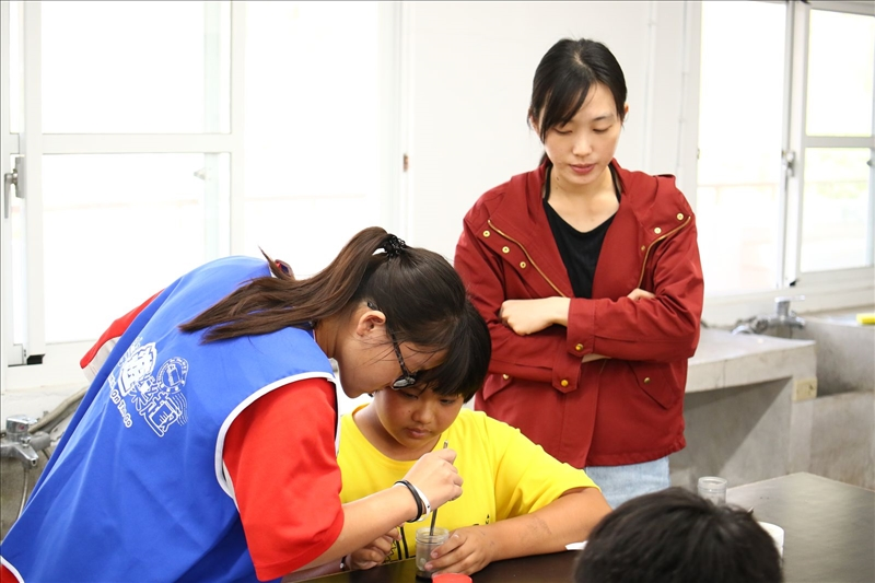 寶來國中單任助手的同學正在教導其他同學如何操作實驗,而老師也在一旁觀看
