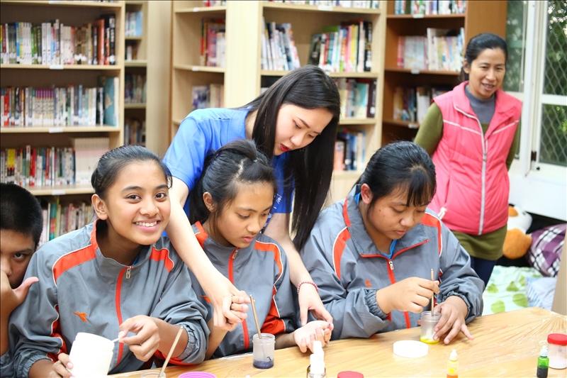 淡江的工作人員正在手把手指導茂林國中的學生如何操作實驗